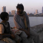 Rajesh Tailang as Mahendra Saini speaks with a child at the Sea Wall in Mumbai in SIDDHARTH. A film by Richie Mehta. A Zeitgeist Films release.
